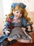 An antique doll. In a blue dress stock photos