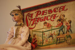 Antique doll. Antique princess doll against a backdrop of an old Spanish toy advertisement Royalty Free Stock Photography