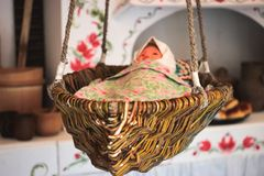 Antique doll lying in a wooden cradle. Antique doll lying in a wooden vintage cradle Royalty Free Stock Photography