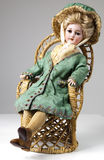 Antique doll in rattan chair Stock Photos