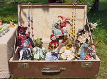 Antique dolls in the suitcase. Old dolls are in a suitcase standing on the grass, outdoors Stock Photos