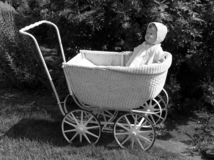 Antique Dolly. Antique doll & carriage in front of old-fashioned rose bush. Vintage garden Royalty Free Stock Images
