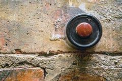 Antique door bell. Old vintage door bell button on grunge brick wall Stock Photos