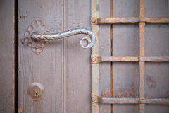 Antique door with handle above crafted with curl Royalty Free Stock Photo
