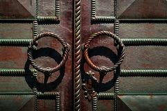 Antique door handle on dark iron door with forged products, concept of authentic objects royalty free stock photography