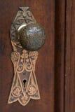 Antique door knob. Closeup of an antique, ornate door knob in wooden door royalty free stock image