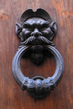 Antique door knob with man's head on old wooden obsolete door Stock Image