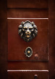 Antique door knocker in the form of a lion's head on old door, R Stock Photos