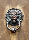 An old lion`s head as a door knocker at the door of a castle stock photography