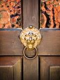 Antique door knocker shaped golden lion's head Stock Image