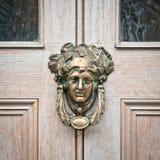 Antique door knocker. An antique knocker on a wooden door Royalty Free Stock Photography