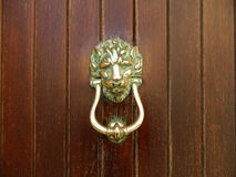 Antique door knocker on a wooden door Stock Photography
