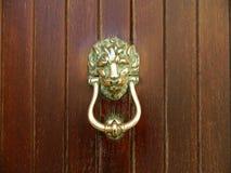 Antique door knocker on a wooden door Stock Photography