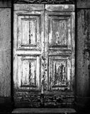 Antique Door In Orvieto. An old, antique wooden door in Orvieto with peeling paint from weathering. (Scanned from black and white film Royalty Free Stock Photos
