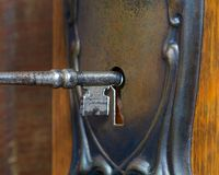 Antique door with skeleton key going into key hole Stock Photos