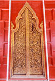 Antique door at Thai temple. This antique door is located at Wat Yai Suwannaram in Petchburi, Thailand. The damage on the upper right hand of the door was axed Royalty Free Stock Photography