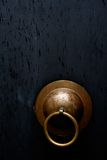 Antique Doorknob. Closeup of an old style doorknob isolated on a black wooden door Royalty Free Stock Images