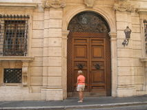 Antique doors on a building in Rome. Antique doors on the exterior of a historic building in Rome with a senior female tourist in the foreground, Italy Royalty Free Stock Photos