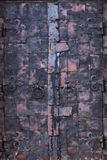 Antique double-leafed door. Double-leafed door stylized for the antique made of aged metal sheets decorated with forged elements in one of the churches in stock photography