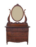 Antique dresser with mirror isolated. Fancy antique oak Victorian wooden dresser, with an oval mirror in a harp frame.  Isolated on white Royalty Free Stock Images