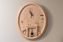 Antique earthen clock on wall. Antique earthen wall clock beige hanging on a white wall stock image