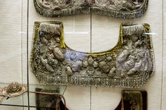 Embroidered Wall Hangings. Antique embroidered textiles hanging on a cladded wall Stock Photo