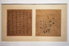 Antique embroidery of calligraphy, flowers and insects. A photograph showing the beautiful old antique style of silk threads embroidered poetry, plants and stock photo