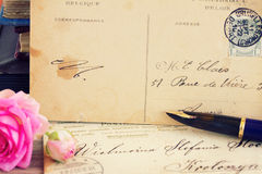 Antique empty postcard with flowers and quill pen Stock Photos