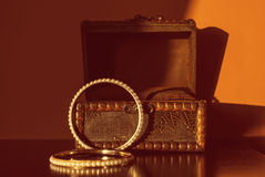 Antique engraved wooden jewelry box and two gold bracelets. Royalty Free Stock Photo