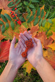 The antique Ethiopian Orthodox traditional cross in the woman's palms. Autumn leaves on background Royalty Free Stock Photography