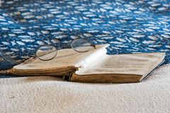 Antique Eyeglasses on Book on Blue and White Bedspread Stock Image