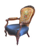 Antique fancy chair isolated. Antique fancy cloth and wood chair with a blue seat cushion, tapestry back, padded arms, carving and scroll work. Isolated on royalty free stock images