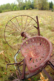 Antique Farm Equipment. An old piece of farming equipment sits idle – abandoned – in a field, reminding us how things were accomplished in the past Royalty Free Stock Photo