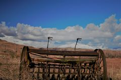 Antique farm equipment in front of snow capped mountains Royalty Free Stock Photography