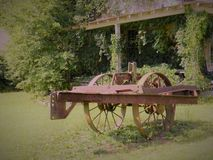 Antique farm equipment old house. Antique farm equipment in front of old house with vines Stock Images
