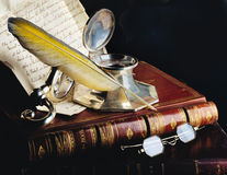 Antique feather pen. With old books, glasses and manuscript Royalty Free Stock Image