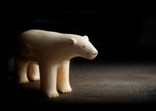 Antique figure of polar bear made of walrus tusk on black backgr Royalty Free Stock Photos