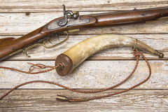 Antique firearm powder horn wood background Stock Images