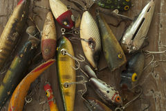 Antique fishing lures on rough wood surface viewed from above stock photo
