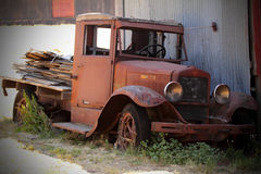 Antique flatbed. A very old parked antique flatbed truck that is turning to rust, still with a load of lumber on the back sitting in weeds. Shallow depth of royalty free stock image