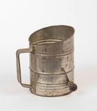 Antique flour sifter. For use in baking, made of tin and wire mesh, photographed on a white background Royalty Free Stock Images