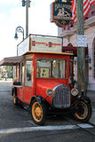 Antique food truck. Classic americana. antique 1920s Ford truck parked on the side of road in front of hotel front and shops, Universal Studios set, Orlando Stock Photo