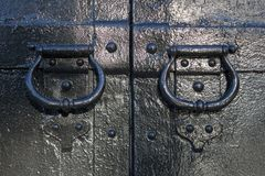 Antique forged handles on the gate stock images
