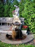 Antique fountain in NJ  Botanical Garden. NJ  Botanical Garden. antique fountain with female figure on top and a cup of water in the sink. early  Autumn time Royalty Free Stock Photography