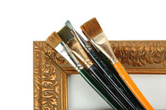 Antique frame and paintbrushes. Isolated on white background stock images