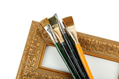 Antique frame and paintbrushes. Isolated on white background royalty free stock image