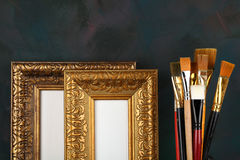 Antique frame and paintbrushes. On painted background royalty free stock photos