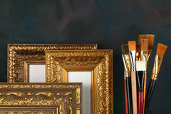 Antique frame and paintbrushes. On painted background stock photography