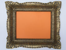 Antique frame painted gold on a orange background Royalty Free Stock Photography