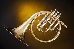 Antique French Horn Isolated. An antique French horn or peckhorn isolated against a spotlight yellow background with copy space Royalty Free Stock Photos
